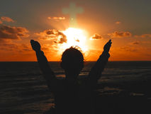 Praising God. A child raising their hands to the setting sun praising God royalty free stock image