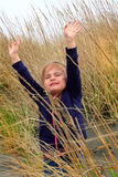 Praising God. A cute little 4 year old girl in tall beach grass with eyes closed lifting hands as if in reverent prayer and praise Stock Image