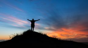 Praising God Sunset. Man Praising God on top of a hill after sunset royalty free stock image