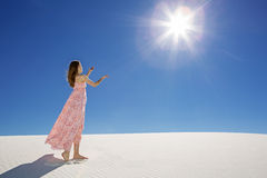 Praising the sun. Young woman in long dress standing in white sand desert with praising hands towards the sun Stock Photo