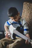 praktijken van de 8 éénjarigen de Britse Indische jongen de elektrische gitaar thuis stock afbeelding
