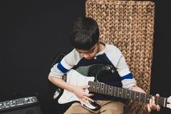 praktijken van de 8 éénjarigen de Britse Indische jongen de elektrische gitaar thuis stock foto