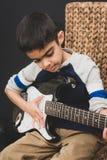 praktijken van de 8 éénjarigen de Britse Indische jongen de elektrische gitaar thuis stock foto's