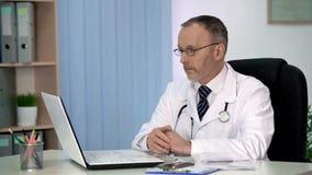 Praktiker, der sorgfältig Medizinartikel auf Laptop, SelbstBildung liest lizenzfreie stockfotografie