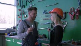 Praktikum in der Autotankstelle, Berufsmechaniker unterrichtet junges Mädchen in Sturzhelm mit Funktionssatz Werkzeugen für stock video
