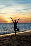 Praktisera yoga för Silhouettekvinna på solnedgång Arkivbild