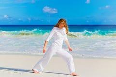 Praktisera yoga för ung kvinna på stranden Arkivbilder