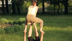 Praktiserande acroyoga för fantastiska par Yrkesmässiga yogainstruktörer övar i en stad parkerar Två lyckade ungdomar arkivfilmer