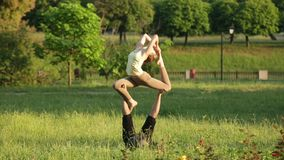 Praktiserande acroyoga för fantastiska par Yrkesmässiga yogainstruktörer övar i en stad parkerar Två lyckade ungdomar stock video