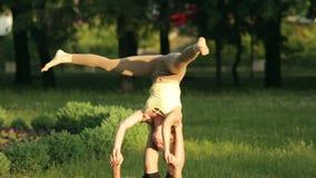 Praktiserande acroyoga för fantastiska par Yrkesmässiga yogainstruktörer övar i en stad parkerar Två lyckade ungdomar lager videofilmer