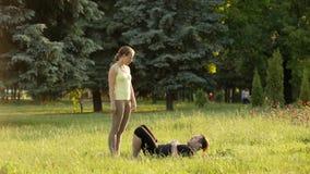 Praktiserande acroyoga för härliga par Unga yogainstruktörer övar i en stad parkerar på grönt gräs Lyckade två lager videofilmer