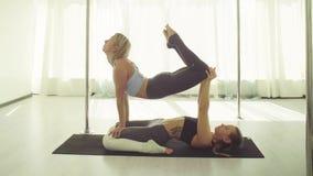 Praktiserande akrobatisk yoga för två unga kvinnor lager videofilmer