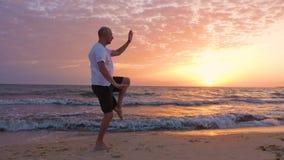 Praktiserande asiatiska kampsporter Tai Chi för idrotts- man på solnedgången över havet stock video