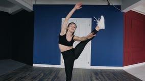 Praktiserande dans för ung härlig caucasian flicka i korridoren, på den röda och blåa väggen för bakgrund Konditionflicka som utb stock video