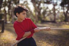 Praktiserande dragkamp för beslutsam pojke under hinderkurs royaltyfria bilder