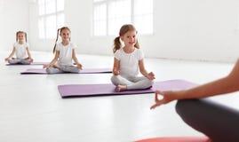 Praktiserande förlovat i gymnastik och yoga med läraren arkivfoto