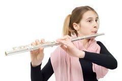 Praktiserande flöjt för ung begåvad flicka inomhus mot vit bakgrund Arkivfoton