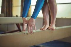 Praktiserande gymnastik för kvinnlig gymnast på balansbommen fotografering för bildbyråer
