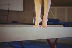 Praktiserande gymnastik för kvinnlig gymnast på balansbommen royaltyfri foto