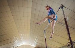 Praktiserande gymnastik för kvinnlig gymnast på horisontalstången fotografering för bildbyråer