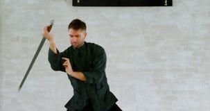 Praktiserande kampsporter för kung fukämpe med svärdet 4k lager videofilmer