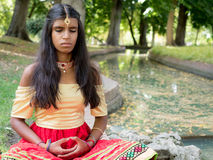 Praktiserande meditation för härlig ung indisk kvinna i parkera Royaltyfria Bilder