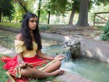 Praktiserande meditation för härlig ung indisk kvinna i parkera Arkivbilder