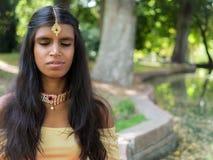 Praktiserande meditation för lycklig härlig ung indisk kvinna i Royaltyfria Bilder