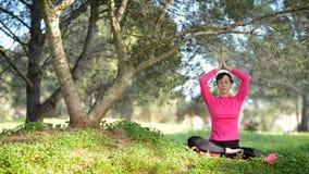 Praktiserande meditation för ung caucasian kvinna i parkera lager videofilmer