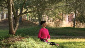 Praktiserande meditation för ung kvinna i parkera arkivfilmer