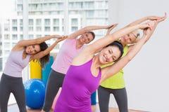 Praktiserande sträckande övning för kvinnor i idrottshall Arkivfoto