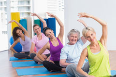Praktiserande sträckande övning för kvinnor i idrottshallgrupp Royaltyfri Foto