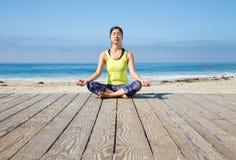 Praktiserande yoga för asiatisk kvinna på stranden Royaltyfri Foto