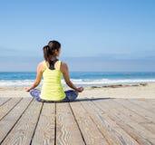 Praktiserande yoga för asiatisk kvinna på stranden Fotografering för Bildbyråer