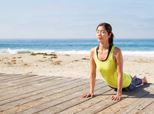 Praktiserande yoga för asiatisk kvinna på stranden Arkivfoto
