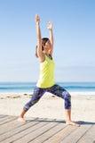 Praktiserande yoga för asiatisk kvinna på stranden Royaltyfri Fotografi
