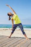 Praktiserande yoga för asiatisk kvinna på stranden Royaltyfri Bild