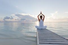 Praktiserande yoga för Caucasian kvinna på kusten Arkivbild