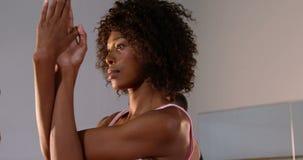 Praktiserande yoga för grupp människor i konditionstudio lager videofilmer