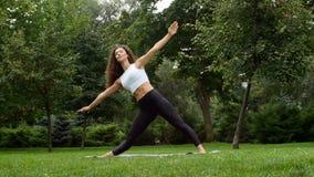 Praktiserande yoga för härlig kvinna i parkera lager videofilmer