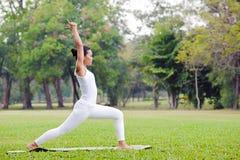 Praktiserande yoga för härlig kvinna i parkera Arkivfoto