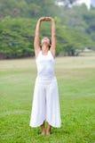 Praktiserande yoga för härlig kvinna i parkera Royaltyfri Fotografi