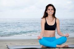Praktiserande yoga för härlig kvinna på stranden Royaltyfri Fotografi