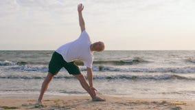 Praktiserande yoga för idrotts- man i fördjupad triangelasana på havskust stock video