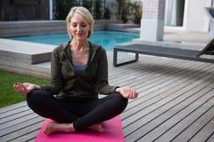 Praktiserande yoga för kvinna i farstubro arkivfoto
