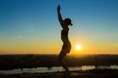 Praktiserande yoga för kvinna i parkera på solnedgången Royaltyfri Foto