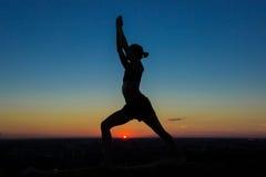 Praktiserande yoga för kvinna i parkera på solnedgången Arkivbild