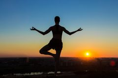 Praktiserande yoga för kvinna i parkera på solnedgången Arkivbilder