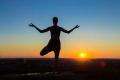 Praktiserande yoga för kvinna i parkera på solnedgången Royaltyfri Bild