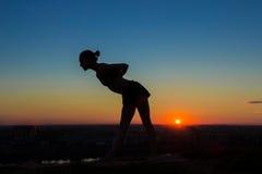Praktiserande yoga för kvinna i parkera på solnedgången Arkivfoton